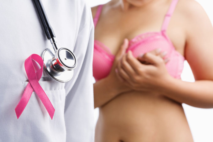 Doctor with pink badge and woman on bra